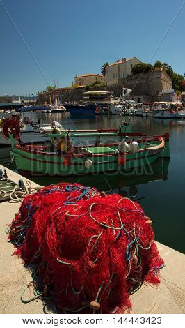 The colorful fishing boat and red fishnet in the foreground Ajaccio fishing port Corsica island France.