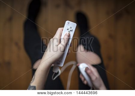 Gothenburg, Sweden - January 17, 2015: A young woman's hands holding Wii remote with Nunchuck, a game pad controller for the Nintendo Wii video game console developed by Nintendo Co., Ltd.