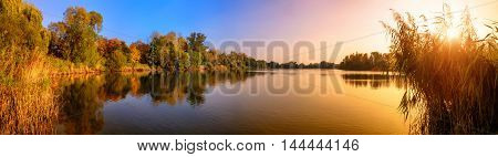 Panorama of a gorgeous sunset at a lake with gold and blue color and trees reflected in the water