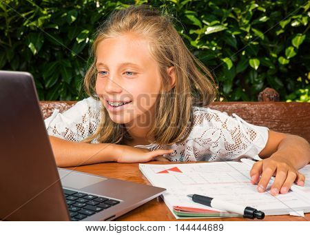 Beautiful teenager student 10 years oldhappiness studying on the computer.