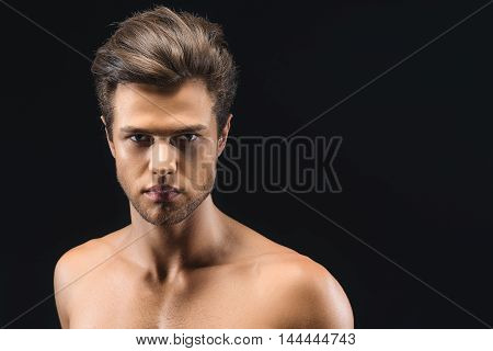 Confident strong man is posing with naked shoulders. He is standing and looking at camera with passion. Isolated and copy space in right side