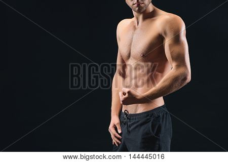Sexy young man is showing his naked trained body. He is straining his muscular arm with confidence. Isolated and copy space in left side