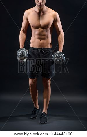 Strong young man is training with dumbbells. He is standing with naked torso. Isolated