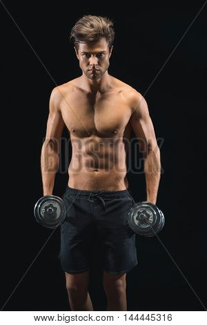 Confident young sportsman is exercising with dumbbells. He is standing and looking at camera with seriousness. Isolated on black background