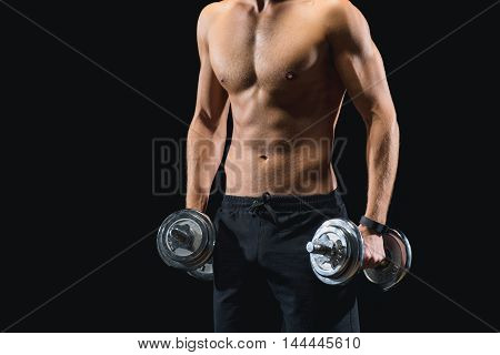 Close up of muscular naked male torso. Young sportsman is lifting heavy dumbbells. Isolated on black background
