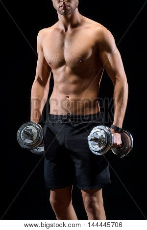 Strong male athlete is standing and exercising with weights. Isolated on black background