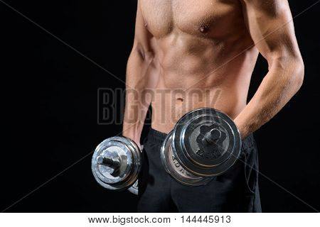 Close up of trained male body. Young man is lifting weights. He has naked torso. Isolated and copy space in left side