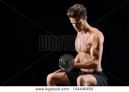 Hard workout. Serious young man is sitting and lifting weight. Isolated and copy space in left side