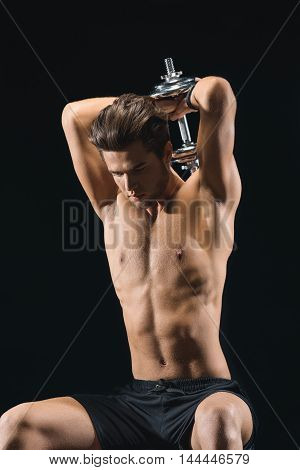 Confident young sportsman is training triceps with dumbbell. He is raising equipment behind his back. Man is sitting and looking forward with seriousness. Isolated