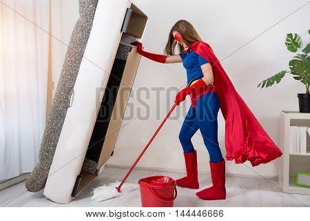 Beautiful Woman Superhero Vacuuming Under The Bed