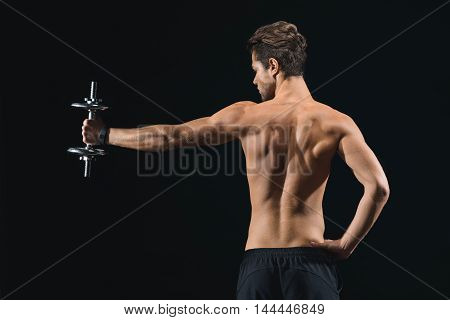 Muscular male athlete is stretching hand sideways with weight. He is standing with arm akimbo. Man is showing his trained back. Isolated