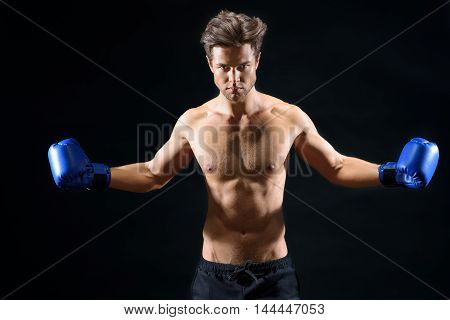 I am a winner. Strong male boxer is stretching arms sideways. He is standing and looking at camera with passion. Isolated on black background
