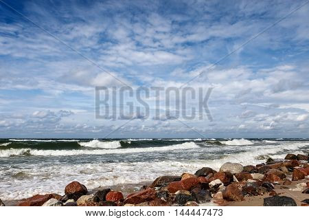 Summer storm at sea. Beautiful waves and white clouds on blue sky