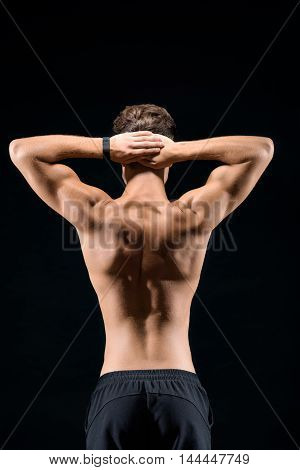 Fit young man is showing his muscular back. He is standing and raising hands behind head. Isolated on black background