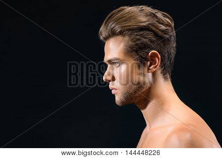 Attractive young man is standing with naked shoulders in profile. He is looking forward with aspiration. Isolated and copy space in left side