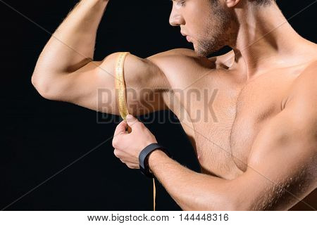 Professional young sportsman is measuring his bicep with tape. He is standing and looking at arm with concentration. Isolated on black background