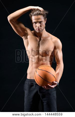 Handsome young man is holding basketball ball. He is standing with naked torso. Man is touching hair and looking at camera with passion. Isolated