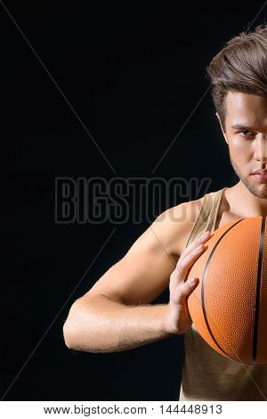 Serious young basketball player is ready for competition. He is standing and holding ball with preparation. Isolated