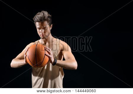 Cheerful young man is playing basketball. He is standing and looking at ball with concentration. Isolated and copy space in right side