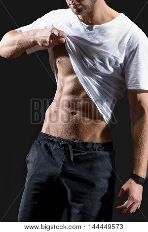 Sexy young man is baring his trained abdomen. He is standing and posing with confidence. Isolated on black background