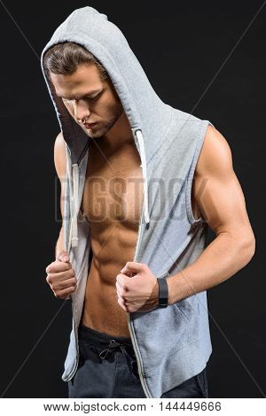 Attractive young man is posing with naked torso. He is touching his clothing and looking down with tranquility. Isolated