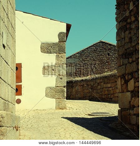 old rough rustic houses and cobblestone road in small portugal village square toned image