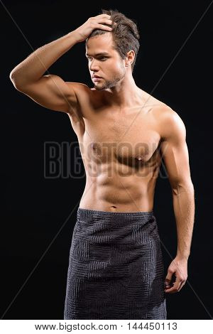 Sexy young man is relaxing after bathing. He is standing and wearing towel. Man is touching his hair and looking aside flirtingly. Isolated