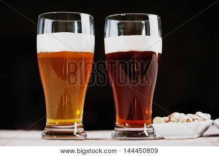 Glasses of beer and pistachio nuts in a white dish