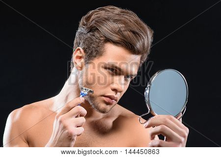 Confident young guy is touching razor to his chin. He is holding mirror and looking at it with seriousness. Isolated on black background