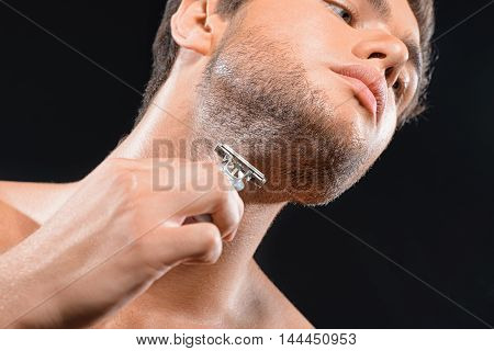 Low angle of young man shaving stubble under near neck. He is standing and looking forward seriously. Isolated