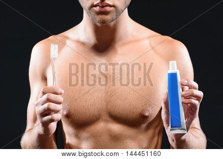 Confident young man is holding toothpaste and toothbrush. He is standing and showing products to camera
