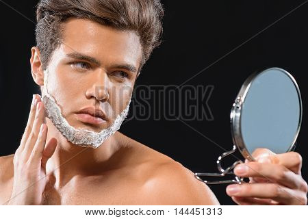 Serious guy is applying shaving cream on his stubble. He is holding mirror and looking at it with concentration. Isolated on black background