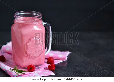 Summer cool drink a smoothie with raspberry and peach on a black background