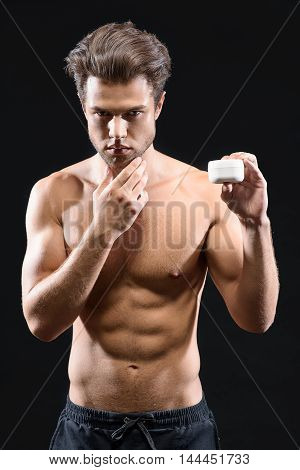 Take care of your skin. Confident young man is showing cream can to camera. He is standing and touching his chin. Isolated