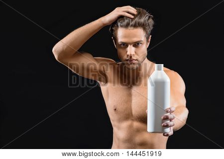 This shampoo is wonderful. Attractive young man is touching smooth hair with enjoyment. He is standing and showing bottle to camera. Isolated