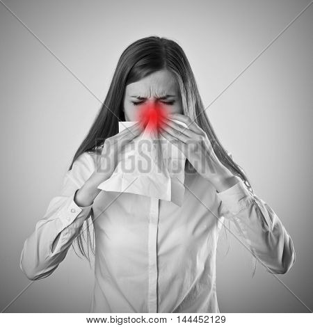 Young woman in white is sneezing. Sneezing.