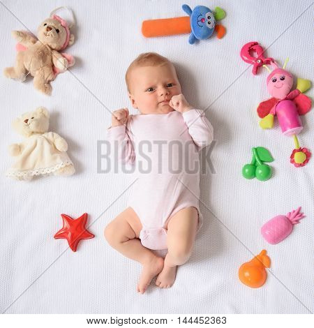 Adorably cute and beautiful. Close up of little cute baby lying on bed with toys around with hand in her mouth