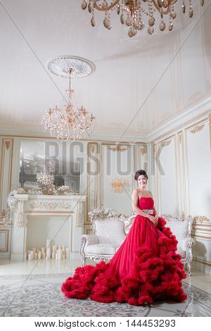 Beautiful woman with blue eyes and curly hair in red dress on luxory interer background with the fireplace and chandelier.