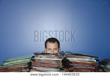 Man hiding behind piles of files at work.