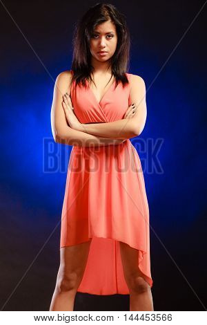 Party clothing evening fashion concept - Portrait attractive fashion woman mixed race girl in orange elegant dress dark blue background
