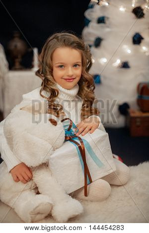 a beautiful little girl holding a gift. The concept of the New Year and Merry Christmas