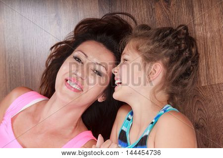 Happy family. Mother mom woman and kid little girl lying on floor at home. Happiness.