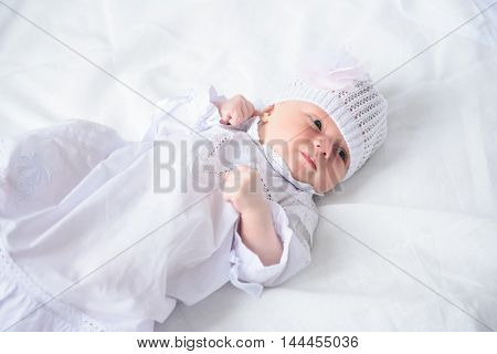 Sleepy little angel. Top view of cute little baby wearing in white dress and knitted hat, lying in bed and looking to side