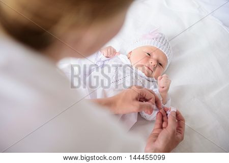Who have is the most beautiful dress. Top view of mother dressing her cute baby girl, lying on bed