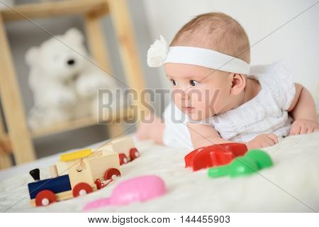 Portrait of adorableness. Close up photo of cute baby girl lying on her stomach on bed beside toys with white elegant headband