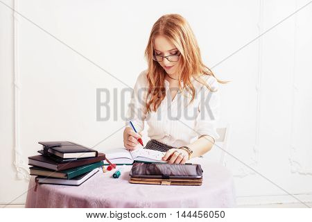 woman takes notes in notepad. The concept of business or education