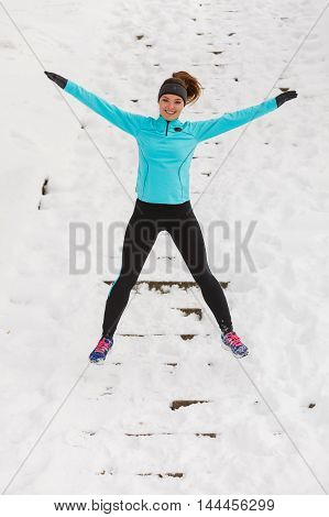 Young Girl Jumping On The Snow.