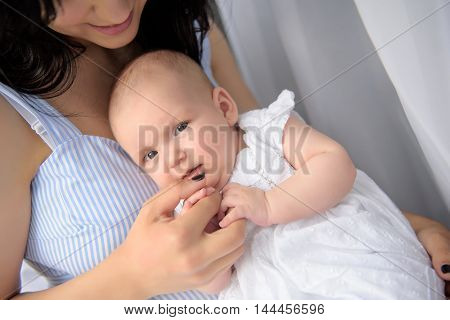 One of the most beautiful bonds ever. Close up of cute little girl lying on her mother tummy and holding hands