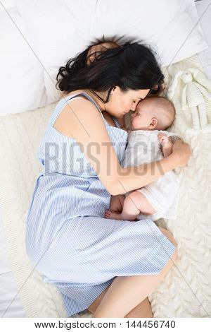 Sleeping peacefully. Cropped shot of young mother hugging her baby while sleeping together in bed