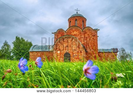Architecture summer cloudy landscape - Church of the Transfiguration of Savior on Kovalevo in Veliky Novgorod Russia. Focus at the church. Architecture landscape with flowers on the foreground.